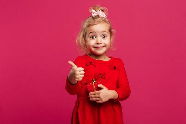 Feliz menina loira de vestido vermelho, aparecendo o polegar