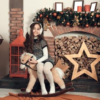 Feliz menina morena com cabelos longos, sentado em um cavalo de brinquedo na sala de natal decorada.