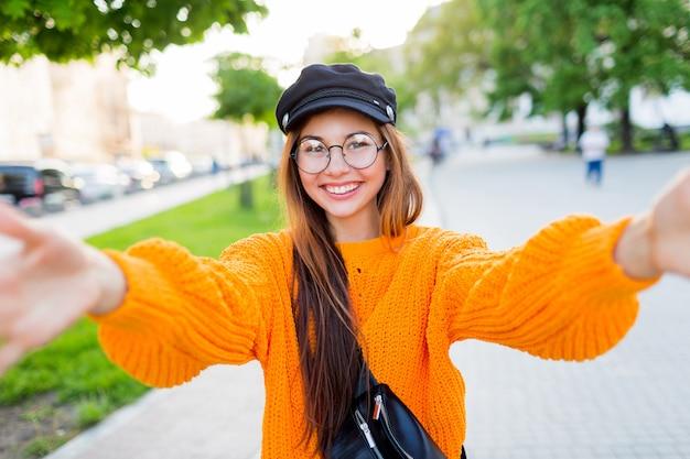 Feliz menina morena sorridente em óculos redondos e laranja na moda camisola de malha fazendo auto-retrato