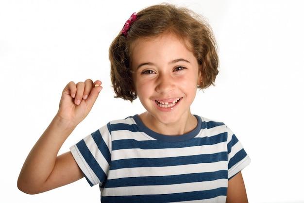 Feliz menina mostrando seu primeiro dente caído.
