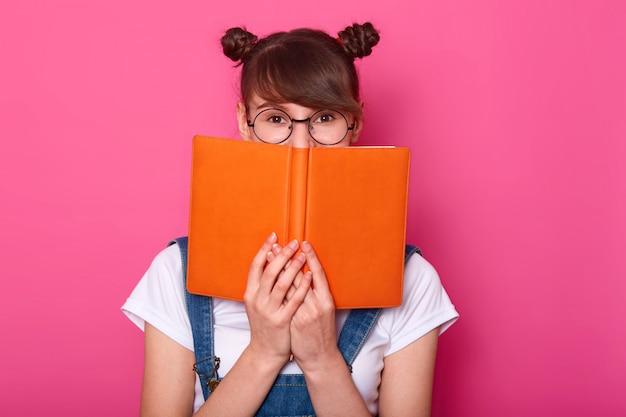 Feliz menina pensativa em pé isolado sobre rosa, segurando o caderno laranja, cobrindo metade do rosto, olhando atentamente para a câmera, tendo cachos, vestindo roupas da moda casuais.
