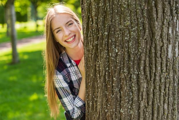 Feliz, menina, posar, atrás de, um, árvore