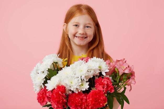 Feliz menina ruiva petite sardas pega suas duas caudas, amplamente sorrindo e parece fofo, usa uma camiseta amarela, segura buquê e fica sobre um fundo rosa.