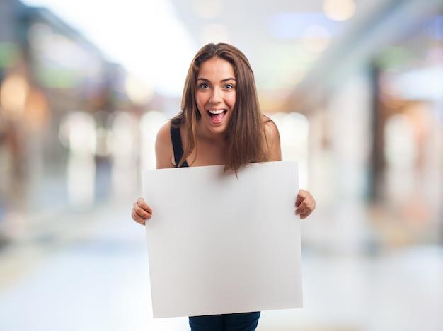 Feliz menina segurando um cartaz em branco