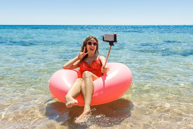 Feliz menina sorridente faz selfie flutuando no donut inflável no mar