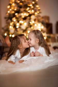 Feliz, meninas, irmã, fundo, de, dourado, bokeh, luzes natal