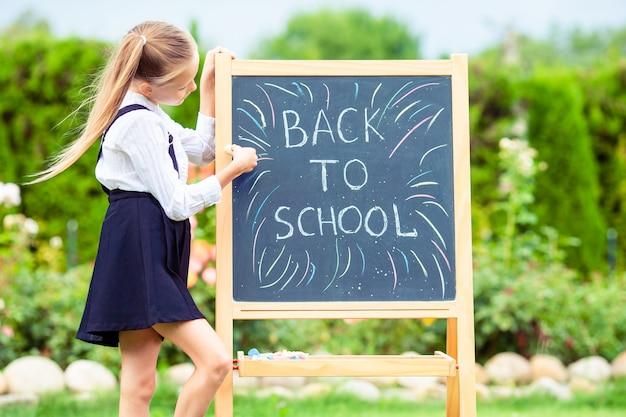 Feliz, menininha, com, um, chalkboard, ao ar livre