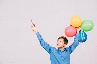 Feliz, menino adolescente, segurando, muffin, e, balões coloridos, levantamento, seu, mão