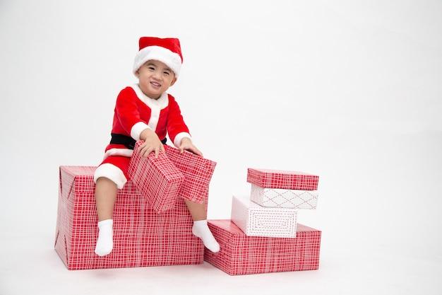 Feliz menino asiático com terno de papai noel segurando uma caixa de presente e sentado na caixa de presente vermelha isolada na parede branca