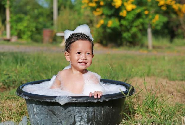 Feliz menino asiático tomar um banho com bolha de espuma na bacia plástica preta na natureza