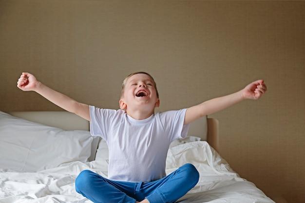 Feliz menino bonitinho alongamento e bocejando na cama branca em um quarto