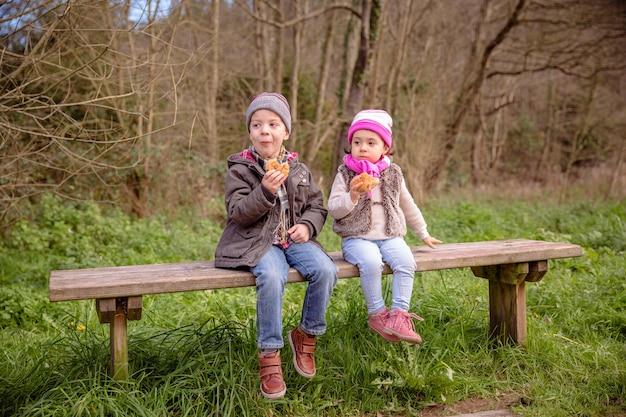 Feliz menino bonito e menina comendo muffins com gotas de chocolate, sentados em um banco de madeira no parque