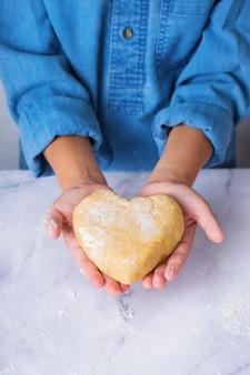 Feliz menino bonito segurando nas mãos um pedaço de massa caseira em forma de coração. tempo para a família na cozinha aconchegante. atividade de inverno em casa. treinamento de ajuda e lição de casa para crianças