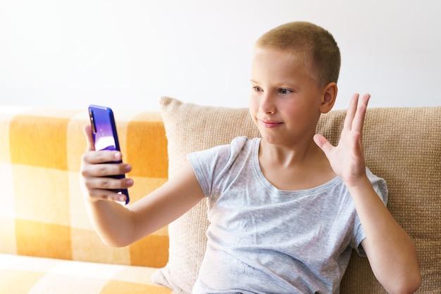 Feliz menino caucasiano com roupas casuais, senta-se no sofá em casa segurando o telefone, olhando para a tela.