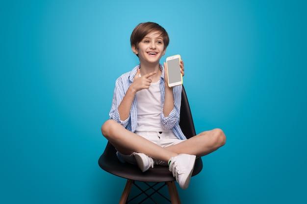 Feliz menino caucasiano com um telefone está sentado na cadeira e apontando para a tela em uma parede azul