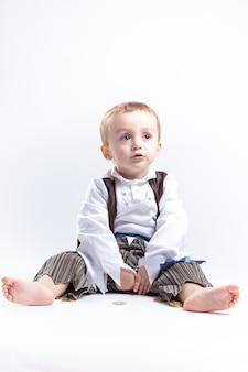 Feliz menino caucasiano, vestido como um pirata, brincando com moedas e confetes. pequeno conceito de menino e trajes.