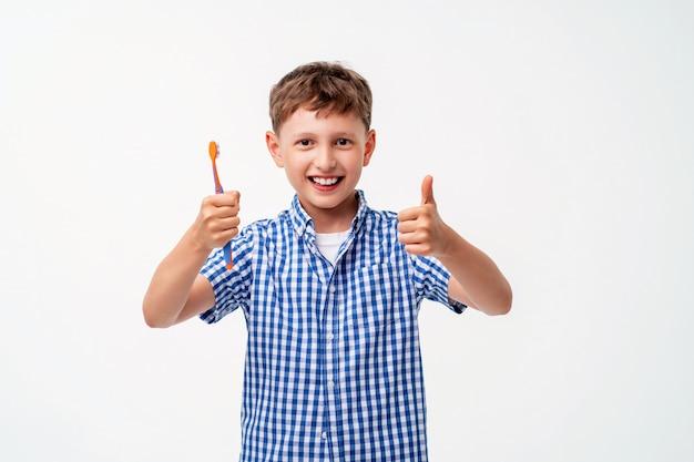 Feliz menino de 7 anos de idade, sorrindo, segurando uma escova de dentes
