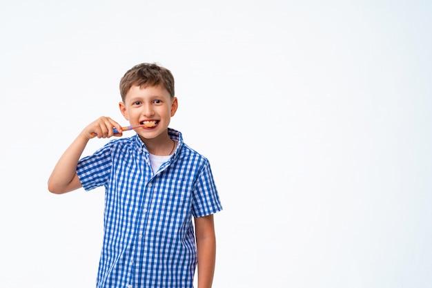Feliz menino de 7 anos, sorrindo, escovando os dentes