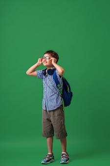 Feliz menino esperto bonito em copos com mochila e fones de ouvido
