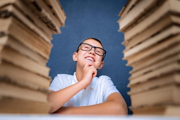 Feliz menino inteligente de óculos sentado entre duas pilhas de livros e olhando sorrindo