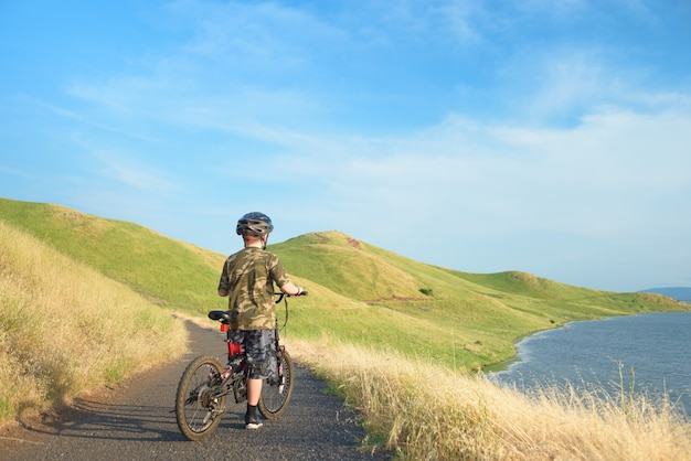 Feliz, menino, montando, seu, bicicleta montanha, ligado, rastro, em, colinas