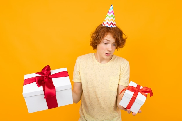 Feliz menino ruivo surpreso com um boné de férias na cabeça com duas caixas de presente em uma parede laranja
