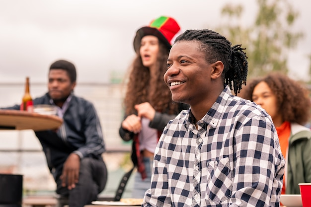 Feliz mestiço de camisa xadrez e amigos assistindo a uma transmissão ao ar livre