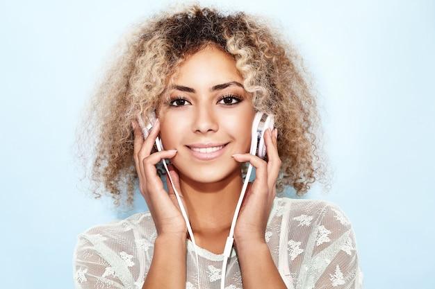 Feliz moda mulher com penteado afro loiro, sorrindo e ouvindo música em fones de ouvido