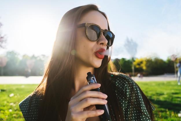 Feliz moda sorridente mulher em óculos de sol fumando vapor na rua, fumo
