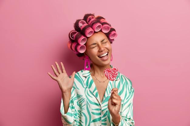 Feliz modelo feminina de pele escura canta e segura pirulito doce como um microfone, levanta a mão, arrepia-se em casa, faz penteado encaracolado, usa roupas domésticas, fica de pé com os olhos fechados e sorriso largo