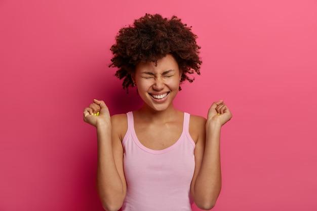 Feliz modelo feminina de pele escura celebra notícias incríveis, levanta os punhos cerrados, sorri amplamente, usa uma camisa casual, posa contra uma parede rosa vibrante, sente-se com sorte e determinada, obteve aprovação