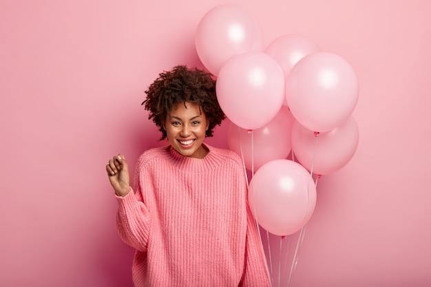 Feliz modelo feminino encaracolado cerra o punho, usa um macacão grande, segura balões de ar, feliz por estar presente na festa de aniversário, usa um suéter rosa em um tom com a parede.