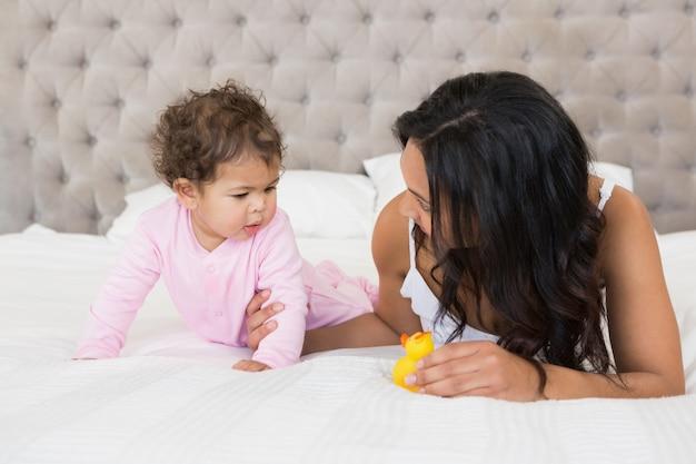 Feliz morena mostrando pato amarelo para seu bebê no quarto