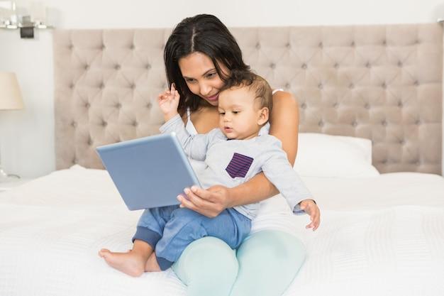 Feliz morena segurando o bebê dela e usando o tablet no quarto