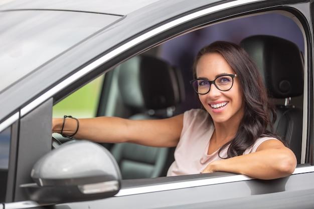 Feliz motorista feminina de óculos sorri para a câmera, segurando o volante com confiança.