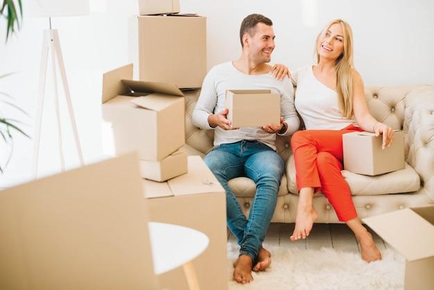 Feliz movido em casal sentado com caixas