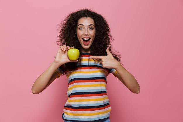 Feliz mulher 20 anos com cabelo encaracolado sorrindo e segurando uma maçã verde isolada na rosa