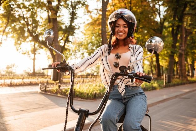 Feliz mulher africana anda de moto moderna no parque e olhando para a câmera