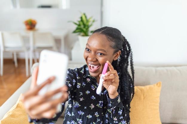 Feliz, mulher africana grávida está mostrando seu teste de gravidez e tomando selfie fazendo videochamada. mulher feliz tirando foto de teste de gravidez com telefone celular e postando foto nas redes sociais.