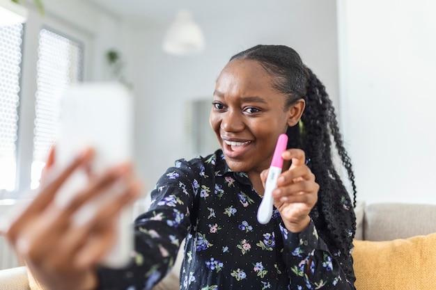 Feliz, mulher africana grávida está mostrando seu teste de gravidez e tomando selfie fazendo videochamada. mulher feliz tirando foto do teste de gravidez com o celular e postando a foto nas redes sociais.