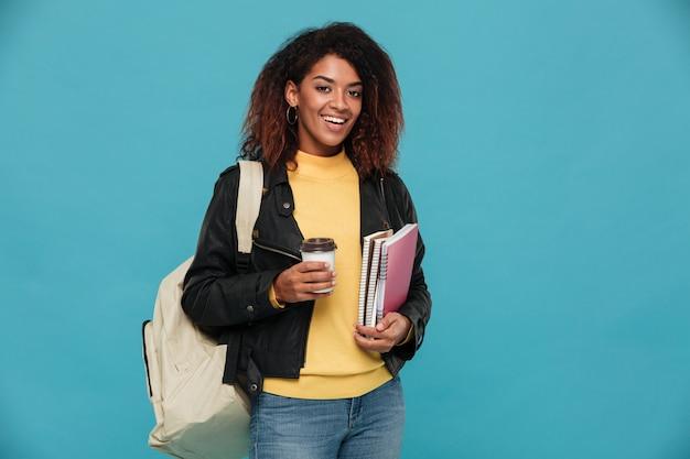 Feliz mulher africana jovem segurando notebooks e café.