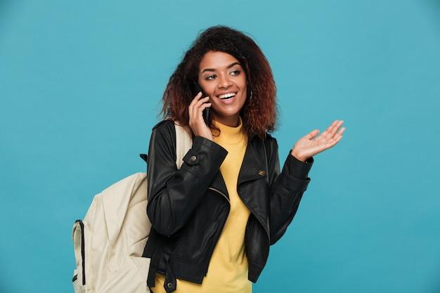 Feliz mulher africana na jaqueta de couro com mochila