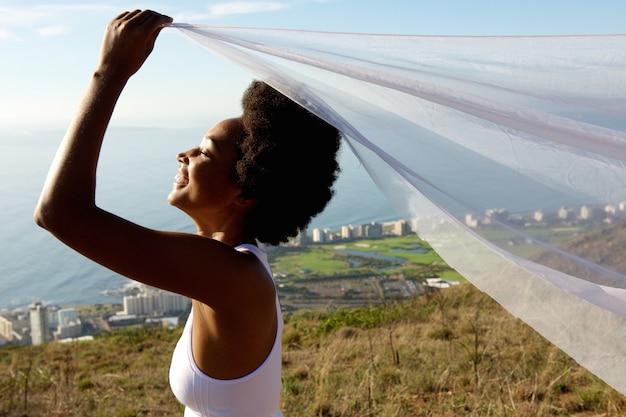 Feliz, mulher africana, segurando, um, echarpe, em, ar
