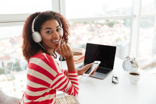 Feliz mulher africana usando smartphone no local de trabalho