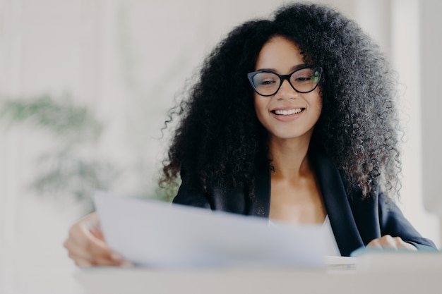 Feliz mulher afro-americana com penteado encaracolado, olha através de documentos