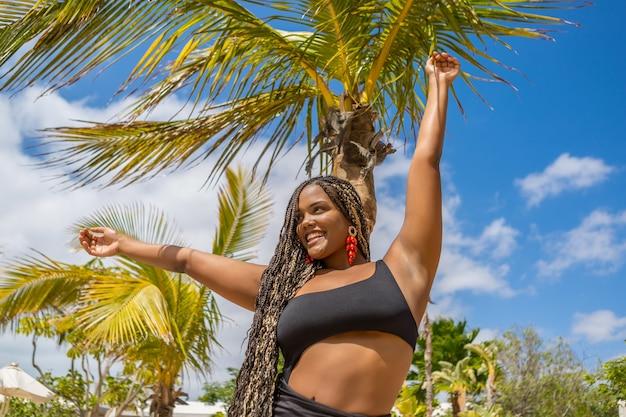 Feliz mulher afro-americana com roupas de verão, com os braços estendidos. mulher alegre na praia sorrindo e olhando para o lado.