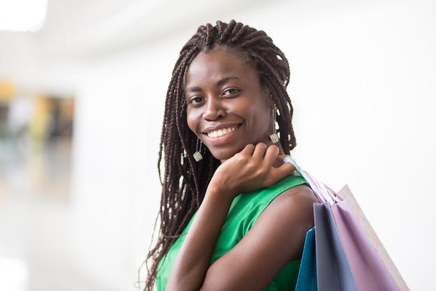 Feliz mulher afro-americana com sacolas de compras