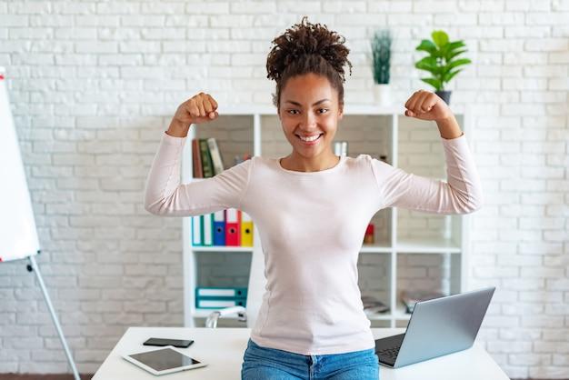 Feliz mulher afro-americana faz um gesto mostrando o bíceps como um atleta