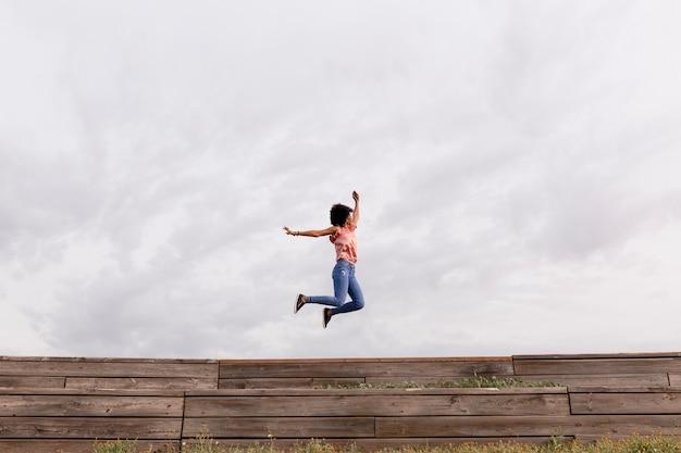 Feliz mulher afro-americana linda jovem ouvindo música em seu telefone móvel e pulando. fundo nublado. primavera ou verão. roupa casual