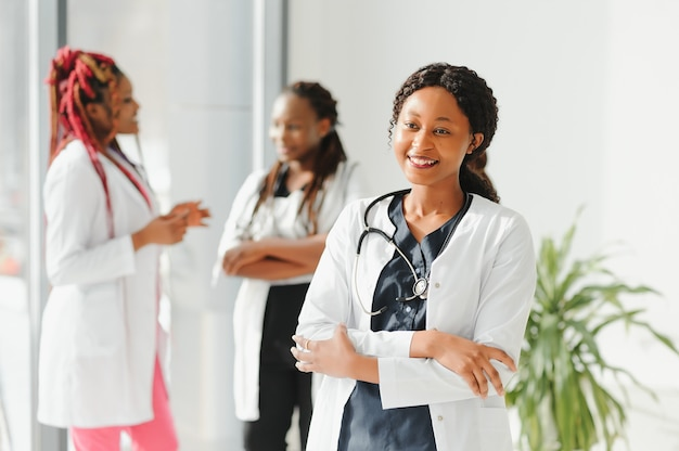 Feliz mulher afro-americana médica ou enfermeira do grupo de médicos que se encontram no hospital